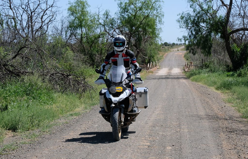 One of the bikers rides along a dirt road on their bike.