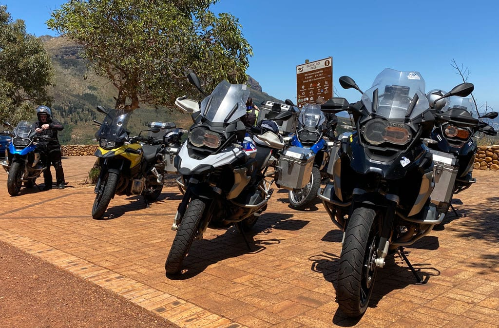 A group of motorbikes parked on a roadside.