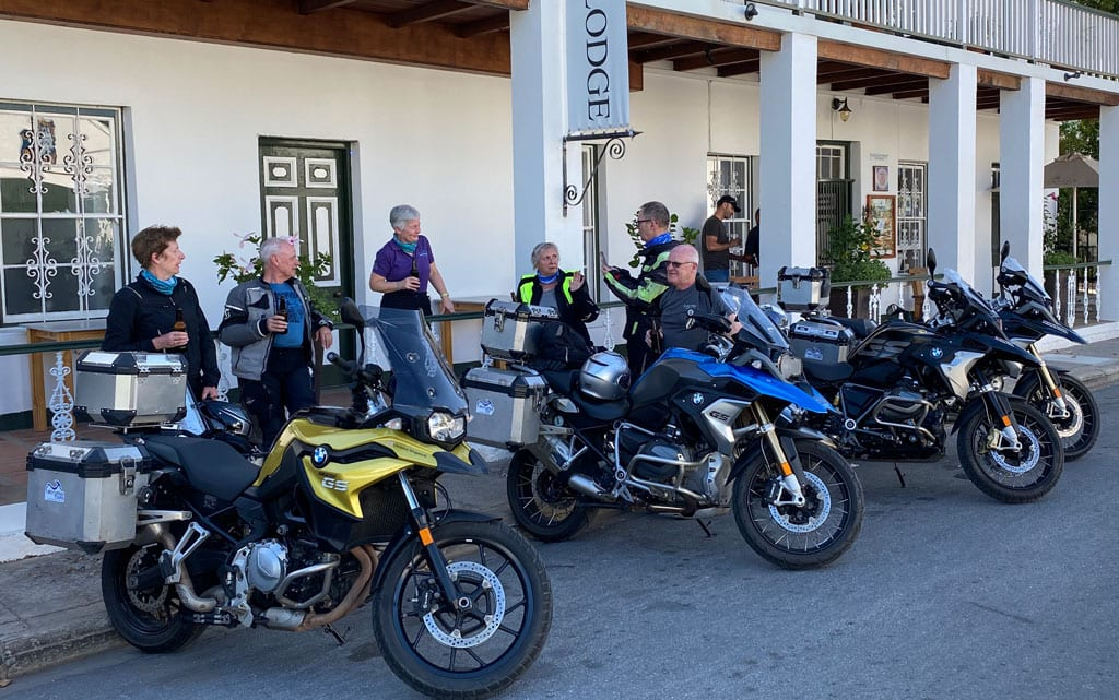 The group have a beer and a chat whilst standing next to their bikes.