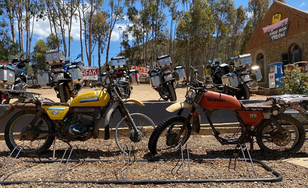 A couple of rusty, retro bikes  displayed outside a motel.