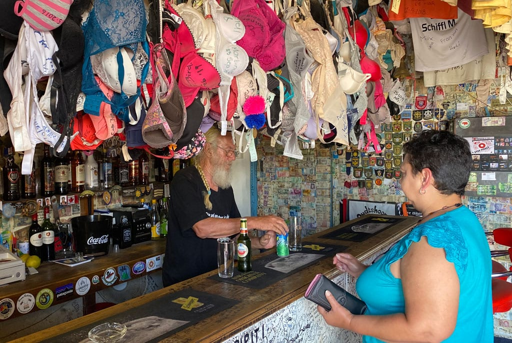 A lady purchasing drinks at a bar with bras hanging from the ceiling.