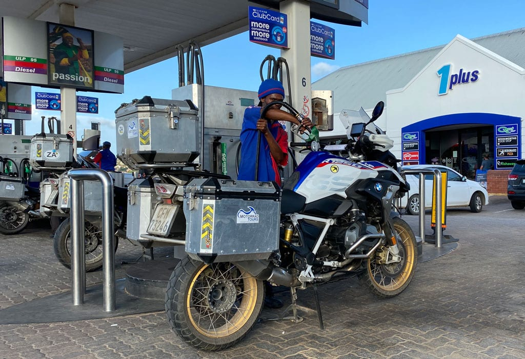 A man fills up one of the bikes with gas.