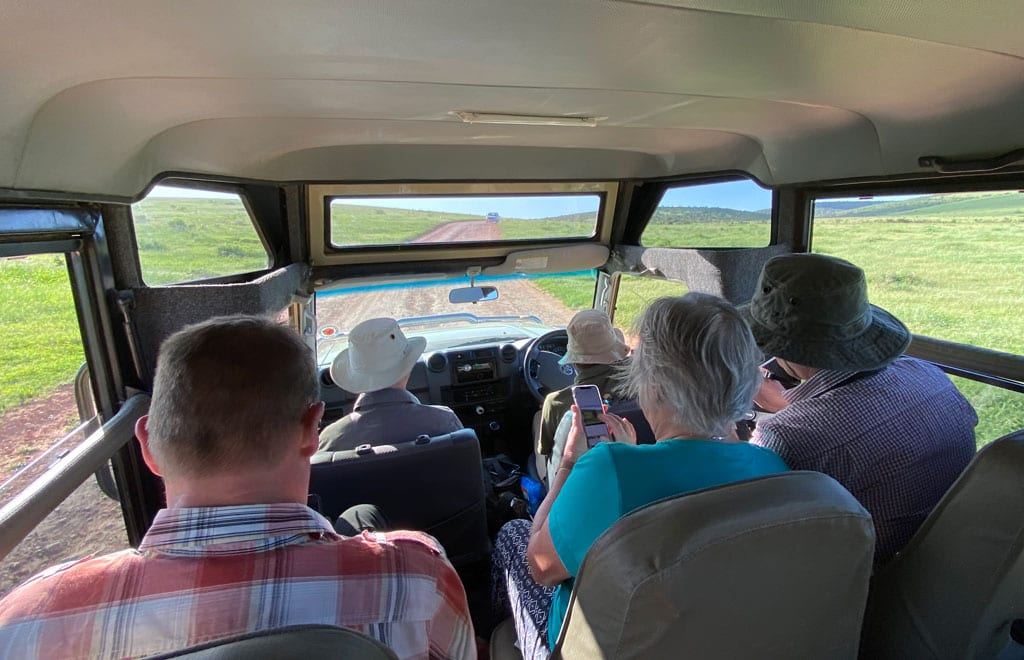 The group sit inside the safari jeep as they travel along a road.