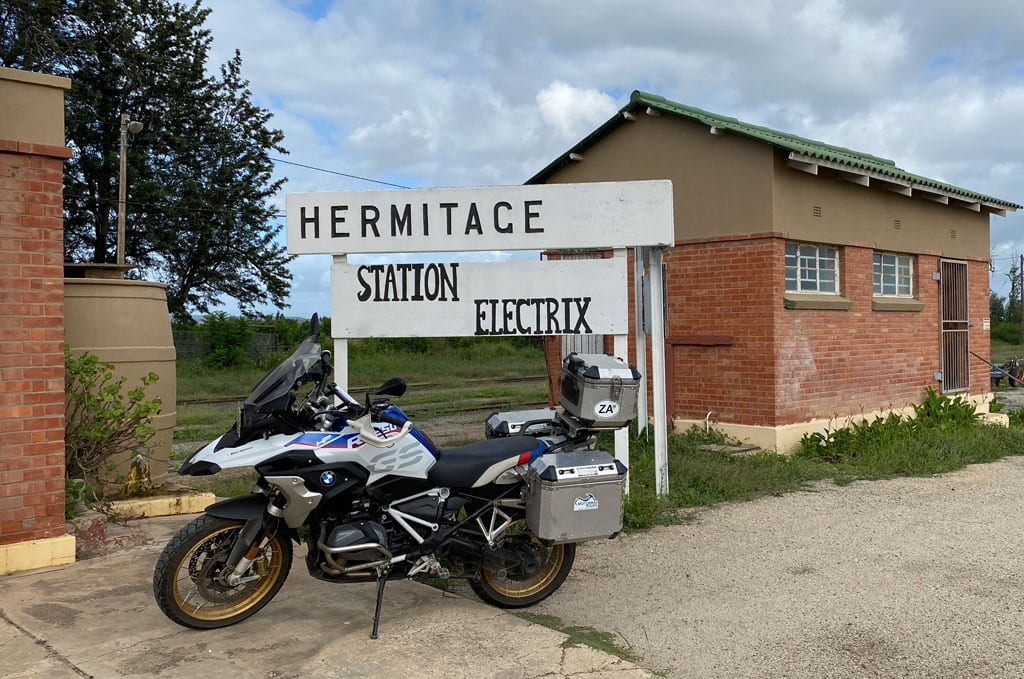One of the bikes is parked outside a small building with a sign that says 'Hermitage, station electric'.