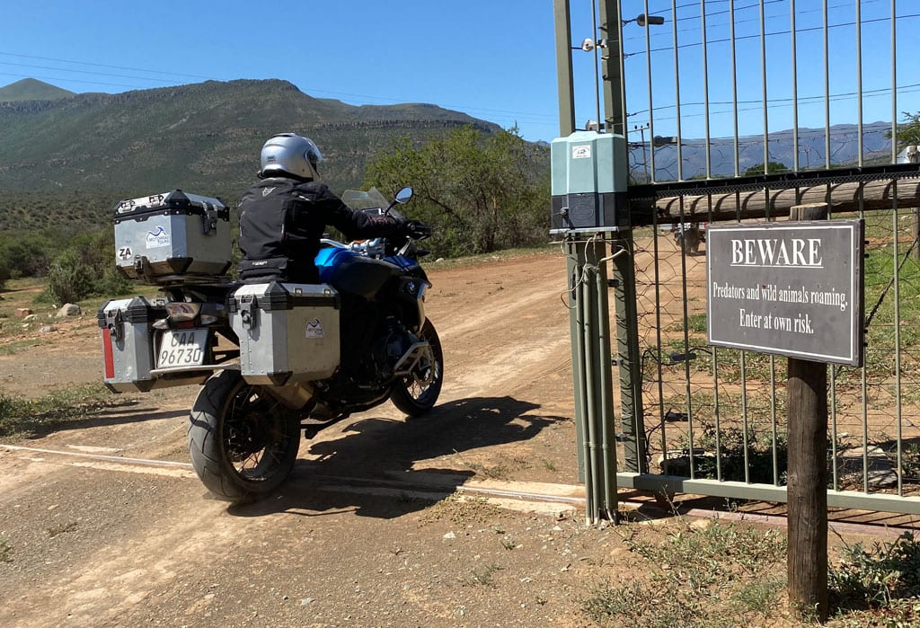 One of the bikers rides into a game reserve. A beware sign stand just outside the reserve's gate.